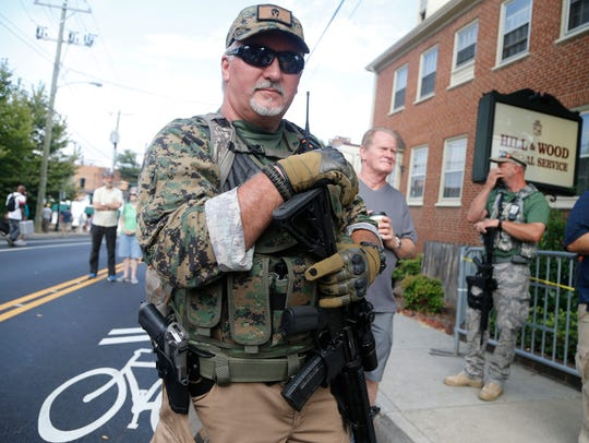 An armed militia member stands guard at a white nationalist