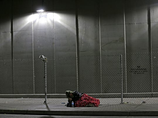 A homeless man rests on a sidewalk under the Smith