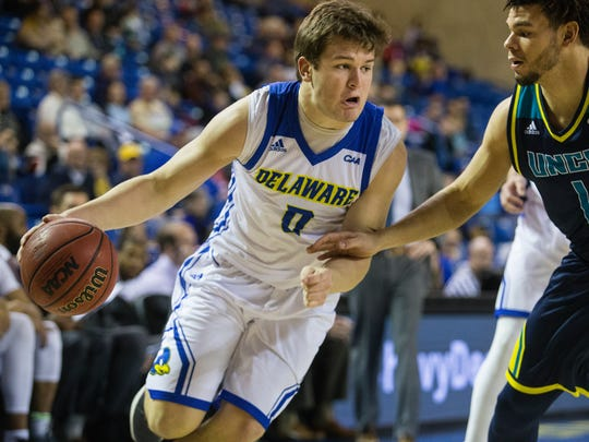 The University of Delaware's Ryan Daly, 0, dribbles down the baseline past UNCW's Jaylen Farnes, 1, Sunday at the Bob Carpenter Center. Delaware defeated UNCW 96-76.