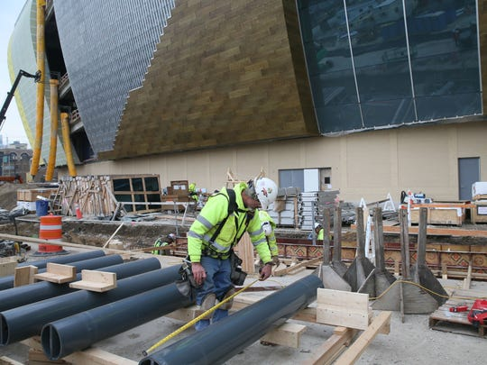 Workers measure bollards that will be part of the anti-terrorism and lighting system outside the new Milwaukee Bucks arena.