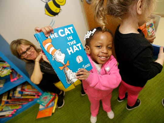 """A child in the Read with Me program holds up """"The Cat"""