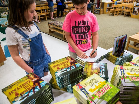 Child author Tommy Belle, 10, signs copies of her book at Eden Park Elementary in Immokalee on Wednesday, April 4, 2018. Hundreds of students, who are a part of The Immokalee Foundation's Immokalee Readers program, received a copy of her and her brother's books after they performed a reading for them.