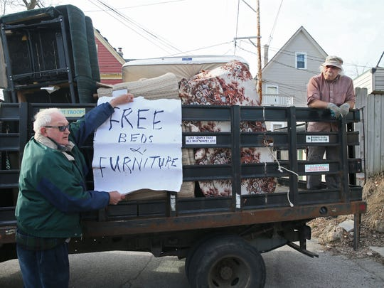 Chris Jaszewski (right) and Don Timmerman of Casa Maria load furniture stored in garages behind Casa Maria onto a truck for delivery. Timmerman holds up a sign that they attach to their truck when they just want to give furniture away.