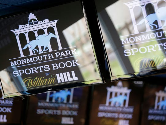 Signs for Monmouth Park are displayed in a bar at the