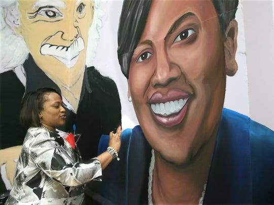 Superintendent Darienne Driver signs her  mural image at James E. Groppi High School on her last day.