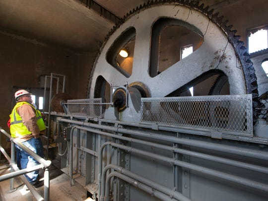 Jim Rand, chief of locks and dams, looks at the gearing installed in the mid-1930s that controls an 86-foot-wide roller gate on the dam at Lock and Dam No. 7.