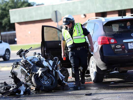 A San Angelo police officer marks the area where a police motorcycle and SUV crashed on Knickerbocker Road on June 25, 2015. Sgt. Korby Kennedy, who had been on the motorcycle, died of his injuries.