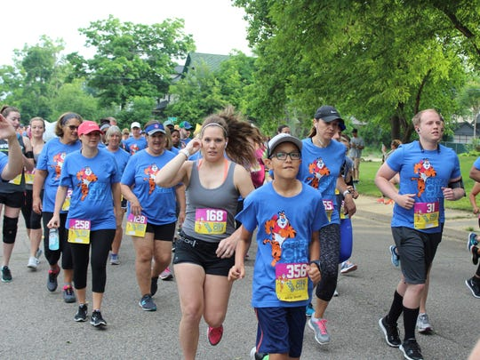 Runners and walkers take off for the start of the Cereal City Classic on Saturday, June 9, 2018.