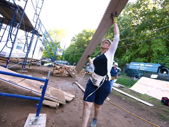 Lourdes Perez, one of the new homeowners helps with
