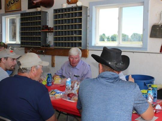 Area organic farmers talk to U.S. Rep. Glenn Grothman (center) during lunch at the Ken Blatz farm.