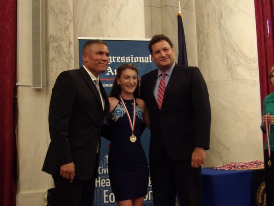 Gina Carvelli, center, of Port St. Lucie, receives the Congressional Gold Medal from Congressional Award National Board Chairman Paxton Baker, left, and Mitchell Draizin, board member.