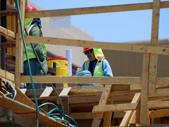 An unidentified construction worker  working on the new building going up on the UTEP campus, prepares to fill a five gallon water container Monday afternoon under the 105 degree El Paso heat. Everyone is reminded to stay hydrated if they are going to be out in the heat. Temperatures are expected to stay in the 100 plus degree zone through Thursday.