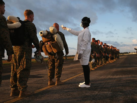 A health worker takes the temperature of U.S. Marines
