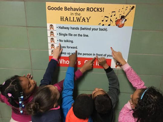 First-grade students at Alexander D. Goode Elementary School point to one of the new posters paid for TBI's Doing Good for Goode project.