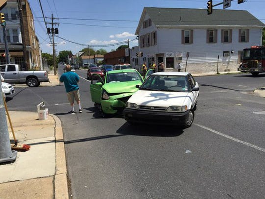 A driver examines a car damaged in a two-vehicle accident Friday afternoon at South Eighth and Locust streets in Lebanon. No injuries were reported.