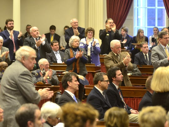 Republican lawmakers stand to applaud, while others