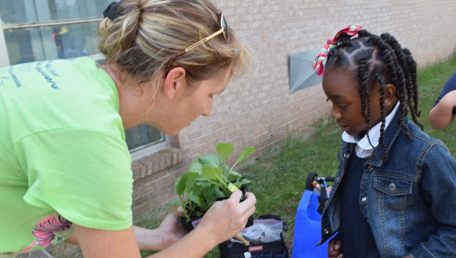 Cindy Baker (left), Good Food Project community garden manager, asks Mabel Brasher third-grader Layla Gray what kind of vegetable plant she is holding. Baker told Layla it is cabbage that was going to be planted in the school's new garden.
