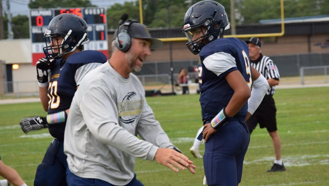 Gulf Breeze High coach Bobby Clayton talks with  Daniel Brayton during a spring game at Dolphin Stadium in 2016.