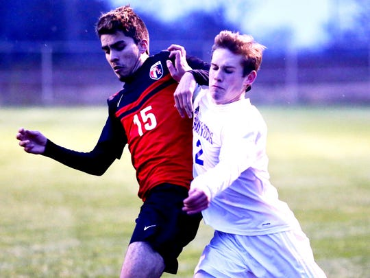 Catholic Central's Ryan Pierson (right) jostles with