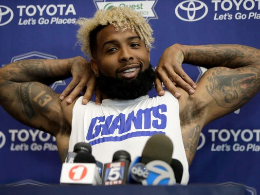 FILE - In this July 28, 2017, file photo, ew York Giants wide receiver Odell Beckham stretches while talking to reporters at NFL football training camp,  in East Rutherford, N.J. Detroit Lions coach Jim Caldwell isn't wasting time worrying whether Odell Beckham Jr. will play for the New York Giants. When Caldwell drew up his game plan for Monday night's contest between the Lions (1-0) and Giants (0-1) at MetLife Stadium, there was a section for dealing with the catalyst of the Giants' offense. (AP Photo/Julio Cortez, File)