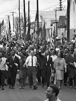 In this March 21, 1965, file photo, Dr. Martin Luther King Jr., foreground, fifth from right, waves as marchers stream across the Alabama River on the first of a five day, 50-mile march to the state capitol at Montgomery, Ala.