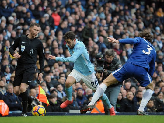 Manchester City's Bernardo Silva, center, challenges for the ball with Chelsea's Marcos Alonso during the English Premier League soccer match between Manchester City and Chelsea at the Etihad Stadium in Manchester, England, Sunday, March 4, 2018. (AP Photo/Rui Vieira)