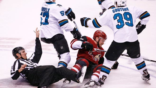 Arizona Coyotes Max Domi (16) and lineman Ryan Gibbons are knocked down by San Jose Sharks Tommy Wingels (57) on Jan. 21, 2016 in Glendale, Ariz.