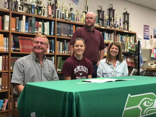 Wall's Anna Pickett, center, listen as her signing