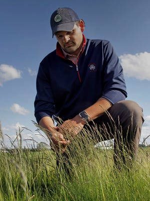 Erin Hills course superintendent Zach Reineking  checks the fescue growing on the 10th green, site of the 2017 U.S. Open.