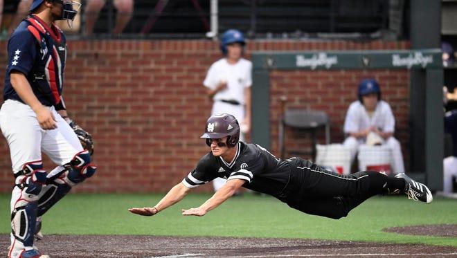 Mississippi State center fielder Jake Mangum (15) dives into home to make the score 2-0 over Vanderbilt at the NCAA Super Regional at Hawkins Field.