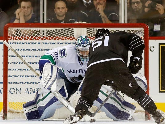 Vancouver Canucks goalie Ryan Miller (30) blocks a shot by New York Islanders center Frans Nielsen (51) of Denmark in a shootout in overtime of an NHL hockey game in New York, Sunday, Jan. 17, 2016. The Canucks defeated the Islanders 2-1 on  right wing Radim Vrbata's winning goal in the shootout. (AP Photo/Kathy Willens)