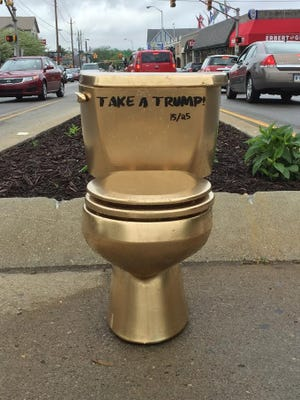 """A golden """"Take a Trump"""" toilet popped up in Broad Ripple on Saturday."""