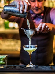 A bartender prepares a cocktail at the Ostrich, the