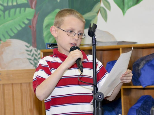 """Fourth-grader Cody Sheehan, a student at New Covenant Christian School, reads his poem """"House Creature"""" at the Lebanon Community Library on Tuesday evening during a reception for the winners of the annual poetry contest.  Cody's poem was one of the winners in the Kindergarten through 8th Grade category."""