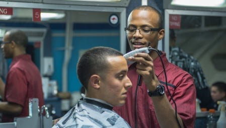 Yeoman 3rd Class Justin Quinones, from Phillipsburg, N.J., gets a haircut aboard the  forward-deployed amphibious assault ship USS Bonhomme Richard.