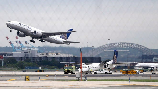 A United Airlines plane, top left, takes off from Newark Liberty International Airport, in Newark, N.J., on July 25, 2013.