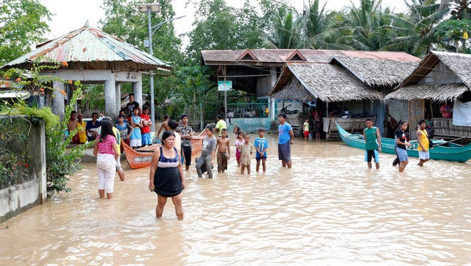 Filipino villagers look on as floodwaters hit the town of Salvador, Lanao del Norte province in the Philippines.