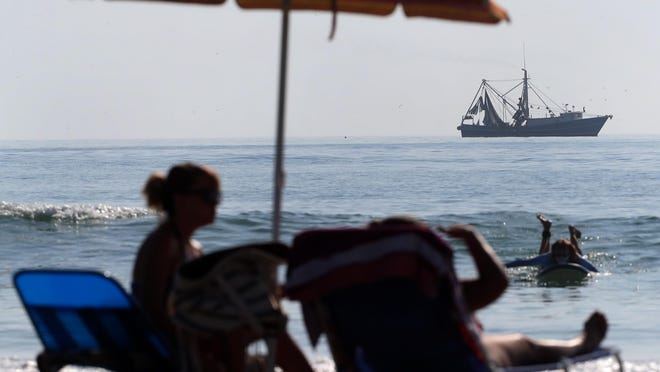 With a shrimp boat not too far offshore, beachgoers enjoy the sun near Andy Romano Beachfront Park in Ormond Beach on Wednesday, June 10, 2020. With last weekend's storms out of the way, forecasters say the area is returning to regular summer weather of high temps and afternoon thunderstorms.