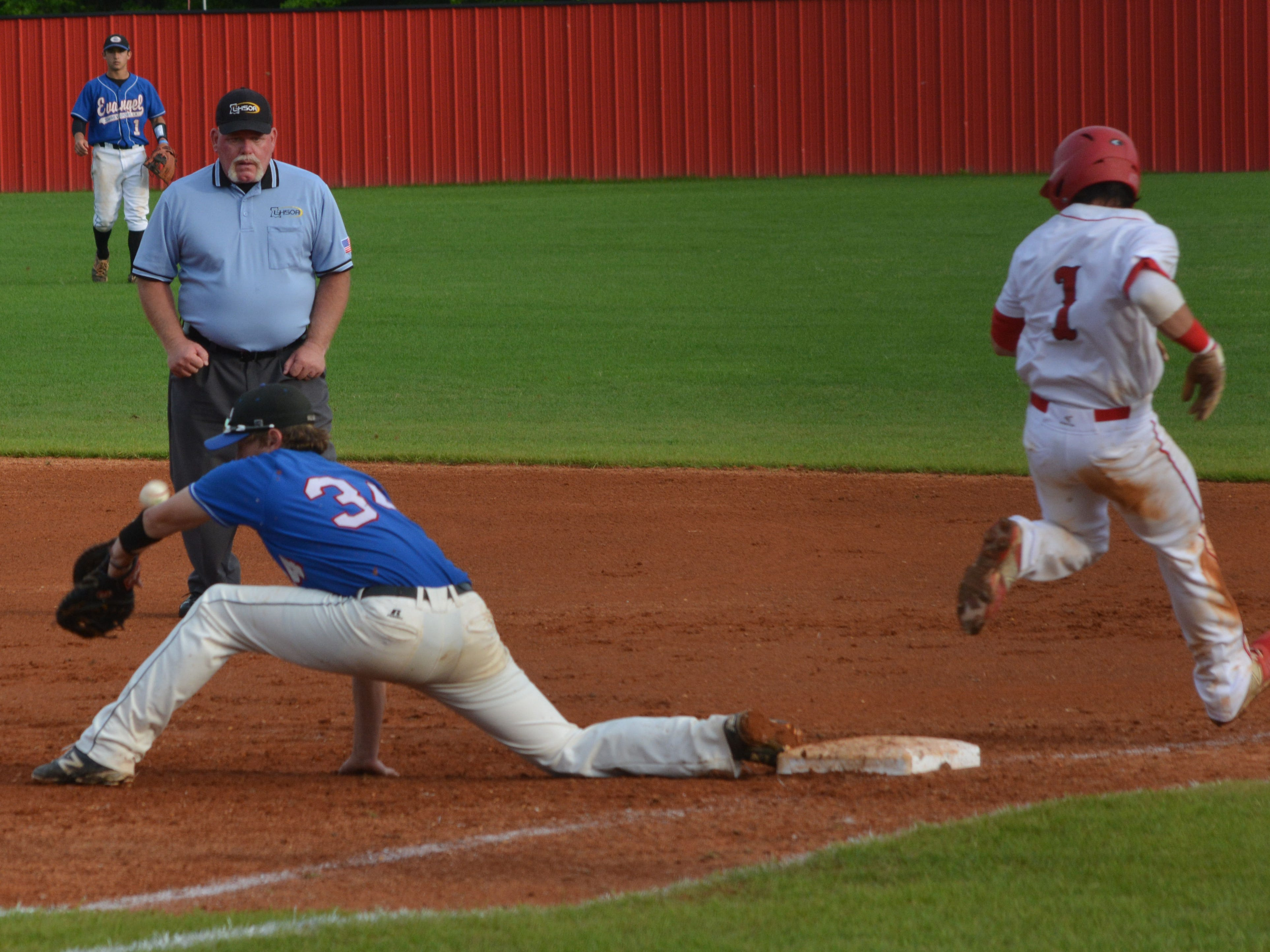 Tioga's Logan Dubois (1, right) is safe at first after the ball bounces off Evangel's Shane Miears' (34) arm Friday.