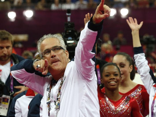 U.S. women gymnastics team's coach John Geddert celebrates in July 2012 with the team after the U.S. won gold in the artistic gymnastics event at the London Olympic Games.