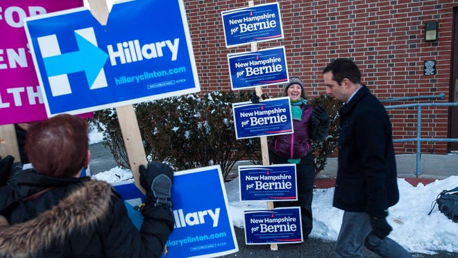 Ellen Fine of Needham, Mass., who formerly lived in New Hampshire for more than 25 years, holds placards in support of Democratic presidential candidate Sen. Bernie Sanders, I-Vt., outside the Ward 5 polling place at the Green Street Community Center in Concord, N.H., on Tuesday, February 9, 2016.