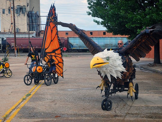 The Bike Zoo, a group of artists, engineers and puppeteers from Austin, pedal their creations downtown Thursday afternoon. They have come to add a fun, creative slant to the Hotter 'N Hell Hundred.