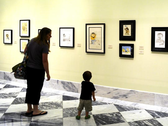 """Catherine Sakarapanee and her son Elliott,1, look at the new Maurice Sendak exhibit celebrating the 50th anniversary of """"Where the Wild Things Are,"""" at the downtown public library's Courtyard Gallery."""