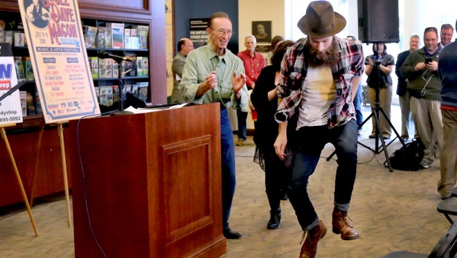 Pickle with the Hogslop String band dances to the sounds of the Slim Chance String Band as local legend buck dancer Thomas Maupin, left, cheers Pickle on during an Uncle Dave Macon Days press conference on, Wednesday, Jan. 27, 2016.