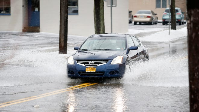 A vehicle drives through standing water on College Avenue, south of Crete Avenue, Tuesday afternoon. A road barrier was placed on Crete Avenue to block access to the road.