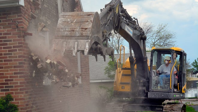 Bernard Anthony, owner of Bernard Anthony Inc., tears down the last of four homes  along Musser Str. in Manchester as part of a multi-million dollar construction project at Thornton Cheverolet, 180 S. Main St. John A. Pavoncello photo