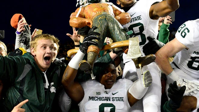 MSU players Montae Nicholson (8, Madre London (28) and Matt Macksood (36) - all still part of this year's team - jump up into the stands to celebrate with the Paul Bunyan trophy and fans after a last-second 27-23 victory over Michigan last year in Ann Arbor.