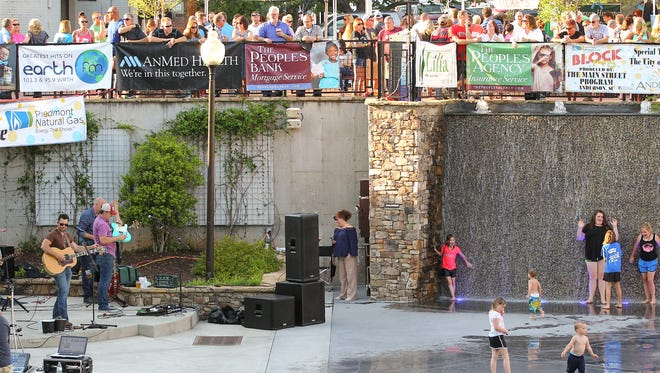 The Eric Scott band plays while adults watch and children play in the Carolina Wren Park water pad during The Main Street Program's Block Party in downtown Anderson.