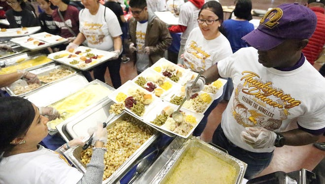 Volunteers served up traditional Thanksgiving meals to the local homeless population and those in need during the 13th Annual El Paso Community Thanksgiving Celebration Thursday inside the El Paso Convention Center Grand Hall.