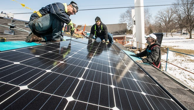 Art Grable, Justin Peterson and Jim Funk of Energize LLC install solar panels Thursday, April 5, 2018 on the roof of Pilgrim United Church of Christ in Fond du Lac.